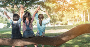 Children friendship concept with happy girl kids in the park having fun sitting under tree shade playing together enjoying good memory and moment of student lifestyle with friends in school time day