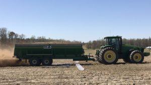 John Deere tracker pulling a litter spreader across a field