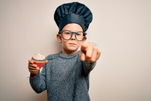 child wearing chef hat, holding a muffin